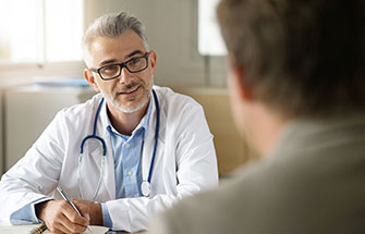 A physician discusses treatment options with a patient.