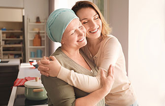 Female patient with head covering and her caregiver embrace affectionately, with their heads side to side.